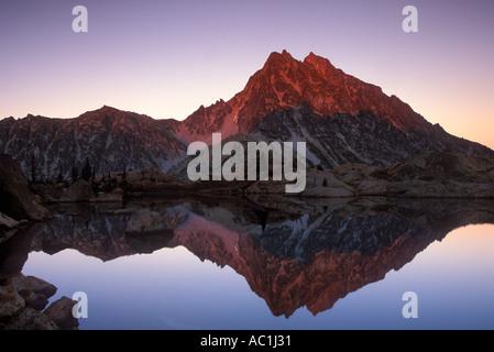 Evening alpenglow on Mt Stuart reflected in the still waters of Ingalls Lake Alpine Lakes Wilderness Washington - Stock Photo