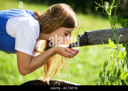 Young woman drinking water from fountain - Stock Photo