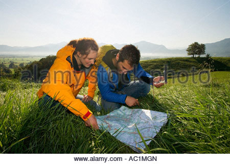 A couple using a map and a compass to find directions - Stock Photo