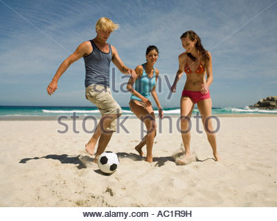 People playing football on the beach - Stock Photo
