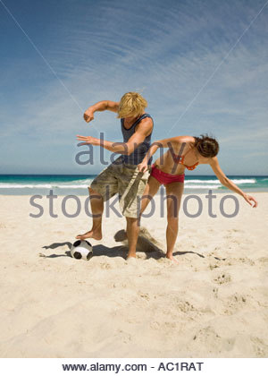 Couple playing football on the beach - Stock Photo