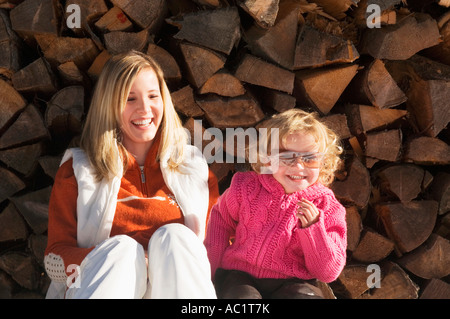 Mother and daughter sitting in front of stack of wood