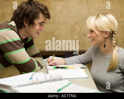 Young woman sitting on desk, looking at young man - Stock Photo