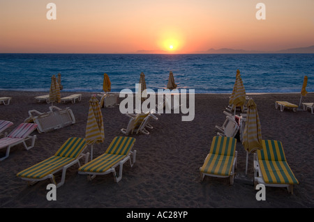 A warm orange sunset across the Aegean sea with sunloungers and parasols on the beach packed up at the end of the - Stock Photo