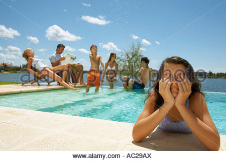 A girl in the pool family in the background - Stock Photo