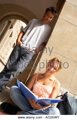A girl and a boy looking at a notepad - Stock Photo