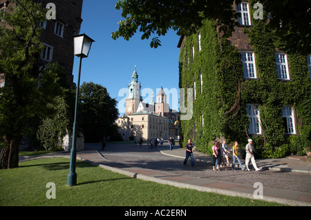 view of wawel cathedral and towers with tourists walking along walkway past streetlight in wawel hill castle krakow - Stock Photo
