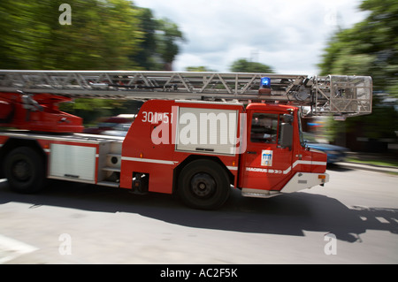 polish fire brigade fire guard straz krakow ladder vehicle speeding past on way to fire - Stock Photo