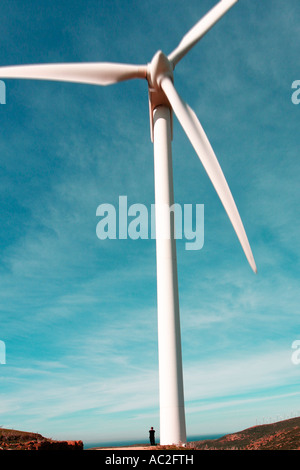 Small figure of man standing at base of huge windmill near Tarifa Cadiz Province Andalusia Spain - Stock Photo