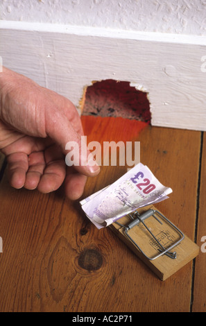 hand reaching out to take money placed on mousetrap instead of cheese outside mousehole in house - Stock Photo