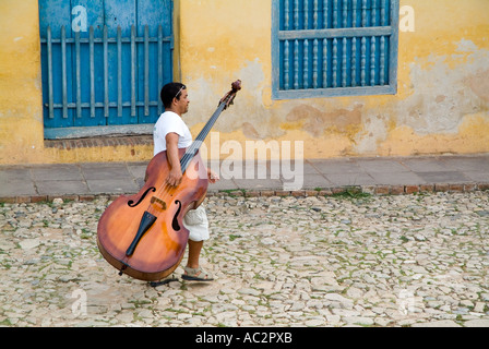 Cuba - Man musician walking down Simon Bolivar carrying a double bass in Trinidad, Cuba - Stock Photo
