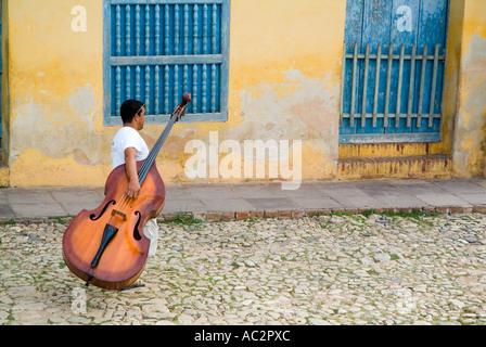 Man walking down Simon Bolivar and carrying a cello, Trinidad, Cuba. - Stock Photo