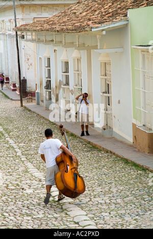 Man musician walking down Simon Bolivar and carrying a double bass, Trinidad, Cuba. - Stock Photo