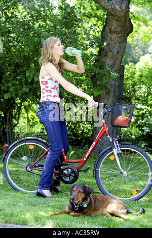 young woman with bicycle and dog is drinking a bottle, Austria - Stock Photo