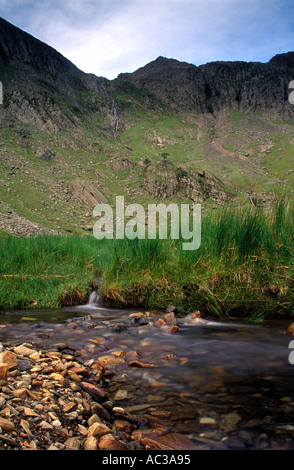 A stream that enters Llyn Idwal with the Glyders mountain range and Devils Kitchen in the background under cloud - Stock Photo