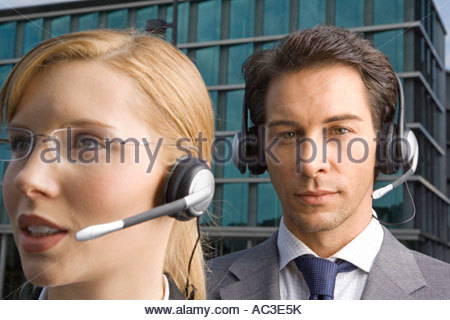 Two business people wearing headsets - Stock Photo