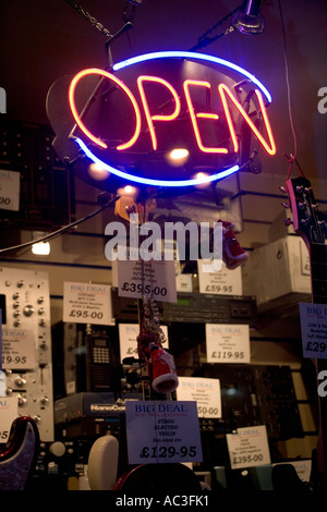 'Open Neon Sign' in the Front 'Shop Window' of a 'Guitar Shop', - Stock Photo