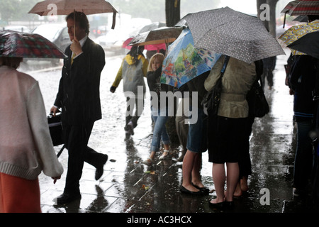 Pedestrians using umbrellas in a summer rain storm on Marylebone Road in London - Stock Photo