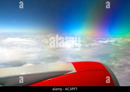 Jet Aircraft window view of red jet engine polarised blue sky and clouds over Europe from 30 000 feet transport - Stock Photo