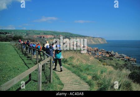 School party walking along cliff top above Robin Hood's Bay village, North York Moors coast, North Yorkshire, England, - Stock Photo