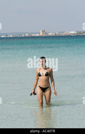 young woman wading from sea with swimming goggles in hand - Stock Photo