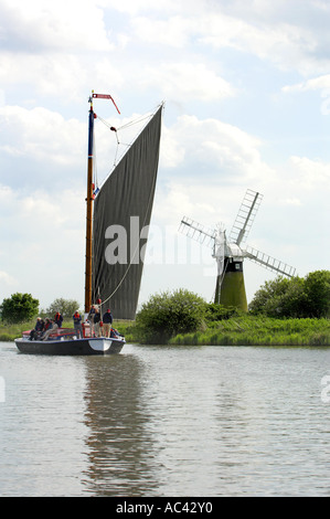 Wherry boat pleasure cruiser on Norfolk Broads with windmill in Background May - Stock Photo