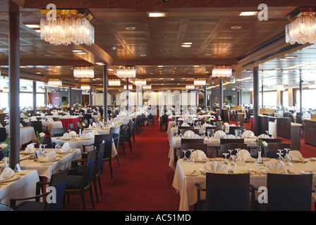 Interior of cruise ship dinning room tables prepared for evening meal - Stock Photo