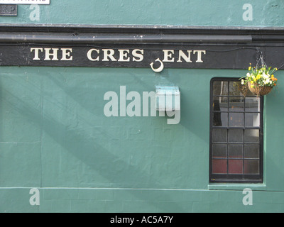 A letter C hanging from a sign saying The Crescent on a pub wall in Brighton East Sussex - Stock Photo