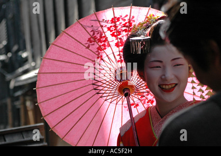 A maiko trainee geisha talks to a man in the Gion district in Kyoto, Japan - Stock Photo