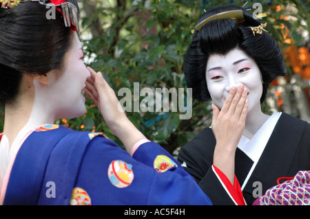 Two maikos trainee geishas laughing in the Gion district in Kyoto, Japan - Stock Photo