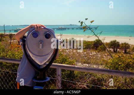 Boy looking through tourist binoculars Fort De Soto Park Florida USA - Stock Photo