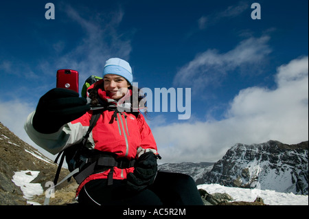 Woman taking a picture on a red camera phone in the mountains - Stock Photo