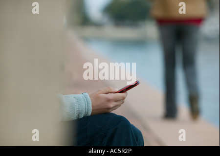 Woman texting on red cellphone - Stock Photo