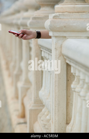 Girl texting on red cellphone - Stock Photo