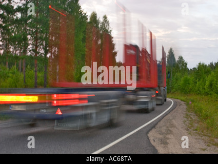 Empty logging truck driving fast at country road , Finland - Stock Photo