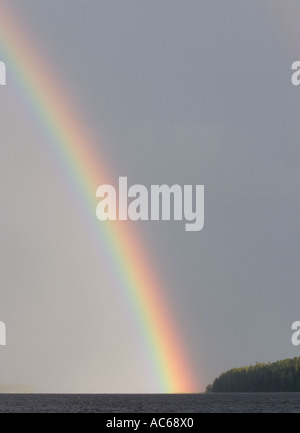 The end of the rainbow hitting spit of land in a lake - Stock Photo