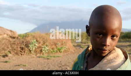 Masai boy at boma/village at Engekaret near Arusha Tanzania. With Mount Meru in background - Stock Photo