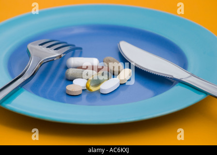 Vitamin pills and dietary supplements on plate with cutlery - Stock Photo