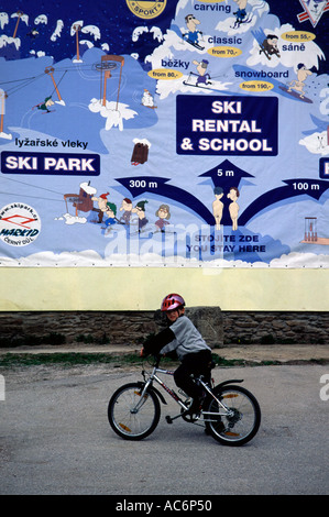 Young boy riding bicycle at the Ski resort in Spindleruv Mlyn a town in the Hradec Kralove Region of the Czech Republic - Stock Photo