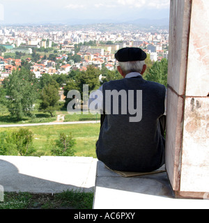 Tirana Albania on hillside overlooking town old man looks out over sprawling city - Stock Photo