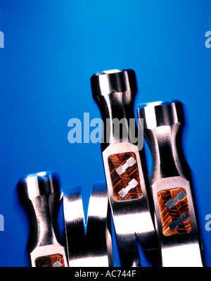 four silver hammers on blue background - Stock Photo
