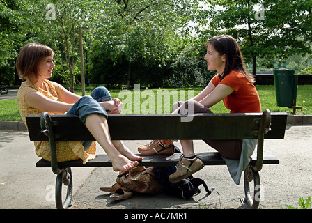 Two girls talking to each other on a bench - Stock Photo