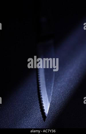 Tip of sharp kitchen knife on black background with spotlight - Stock Photo