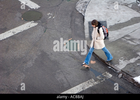 A woman begins walking across a street in Lincoln, Nebraska. - Stock Photo