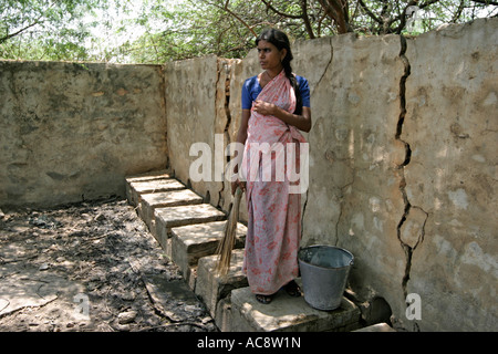 A dalit, or 'untouchable' woman, cleaning public lavatories in her town in Andhra Pradesh, India. - Stock Photo