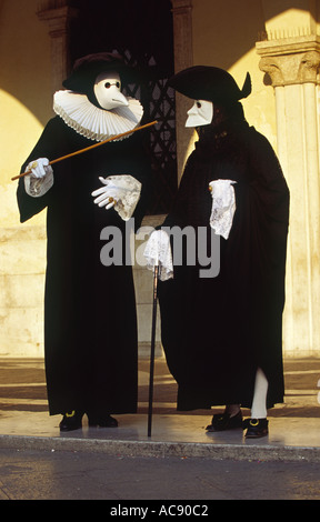 Participants in Venice Carnival wearing traditional Il Dottore and Bauta masks Italy - Stock Photo