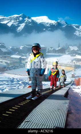 Children skiing on a moving belt ski lift at Wengen Switzerland - Stock Photo