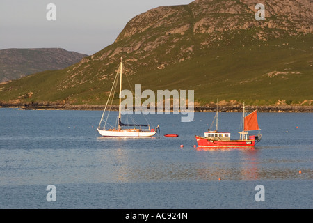 Small yacht and fishing boat moored in The Eastern bay of the isthmus on Vatersay, Outer Hebrides - Stock Photo
