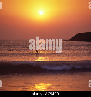 A single surfer sitting on his board silhouetted against the sinking yellow ball of sunset at Saunton Sands beach - Stock Photo