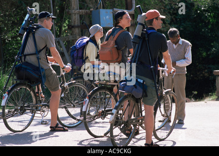 Keen ornithologists ecotourists on bikes arriving at ticket post at gate of Keoladeo Ghana NP Bharatpur Rajasthan - Stock Photo